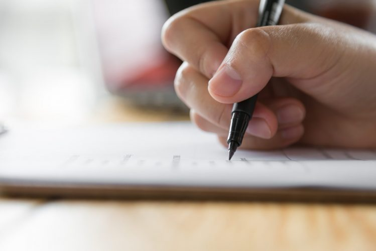 hand-writing-on-paper-with-pen-min